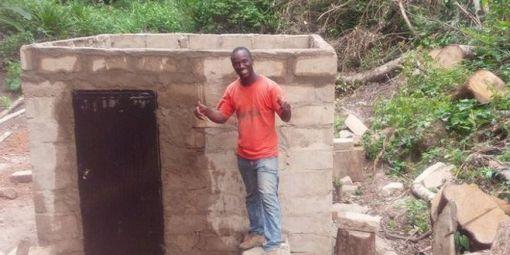 Ibrahima Tounkara devant le micro-barrage hydroélectrique qu'il a construit de ses mains dans son petit village de la région de Guéckédou (sud de la Guinée). © Guinéeinfos