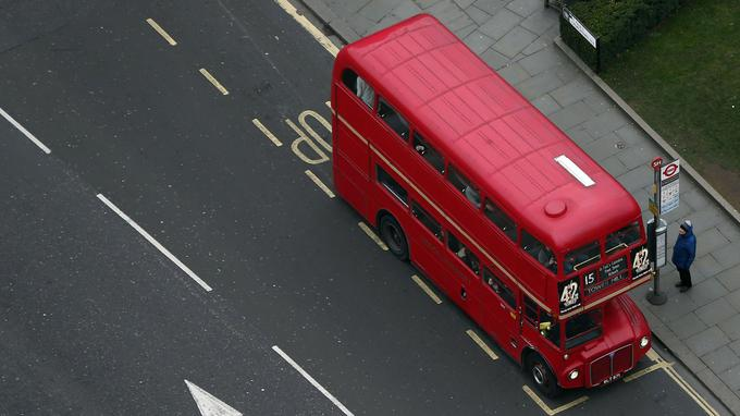 A traditional Routemaster bus picks up a passenger in London, Britain February 25, 2017. REUTERS/Neil Hall - LR1ED2P1A8A7U